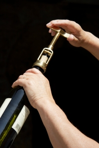 Hand uncorking a wine bottle